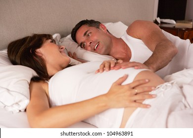 Pregnant woman and husband in bed