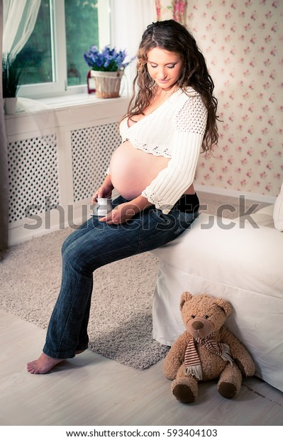 A pregnant woman in jeans and a skimpy jacket sitting on a sofa next to a teddy bear