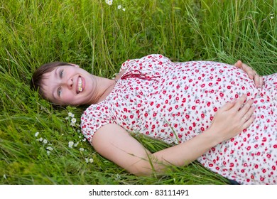 Pregnant woman lie in chamomile and grass background