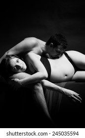 pregnant woman lies on the hands of her husband, who kisses her belly. black and white