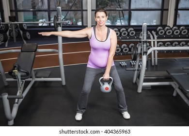 Pregnant woman lifting kettlebell at the gym