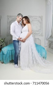 Pregnant woman in long dress and man stand together in bedroom