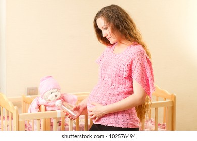 Pregnant woman with long hair feeding from a bottle with a nipple toy Teddy bear in a crib