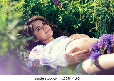 Pregnant woman lying in a meadow with lupines and touching her growing pregnant belly