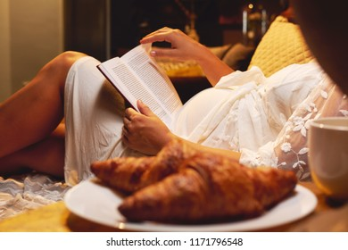 Pregnant woman lying on the bed at bedroom and reading a book about maternity or chicklit, womans novel at home, focus on a belly and book. Lifestyle, free time good habits concept.