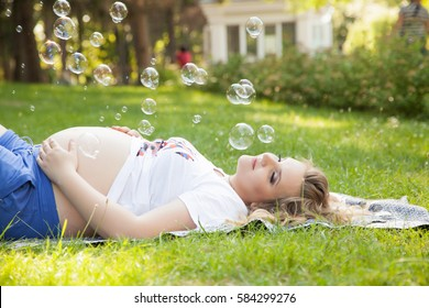 Pregnant woman lying on the grass and fly over it bubbles