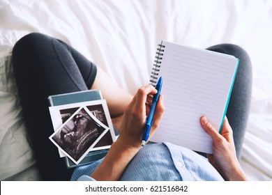 Pregnant woman makes notes in notebook and holding ultrasound image and medical documents at home interiors. Pregnancy, parenthood, preparation and expectation concept. Close-up, copy space, indoors.