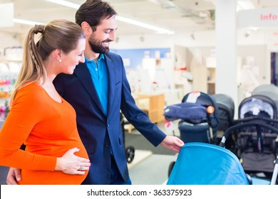Pregnant woman and man in baby shop looking for stroller to buy