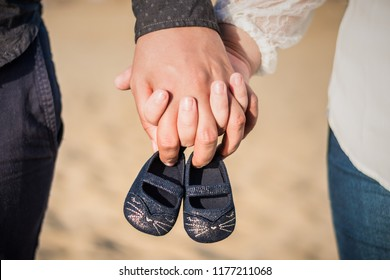 Pregnant woman and man holding baby shoes in hands. Future mom and dad, parents is holding little newborn baby shoes. Birth expectation concept. Waiting of baby. Pregnant woman, pregnancy, mother