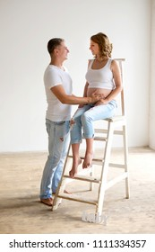 Pregnant woman and man at jeans