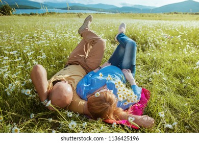 pregnant woman and man lie on green grass, happy young couple