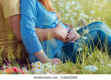 pregnant woman with man outdoors, belly close up