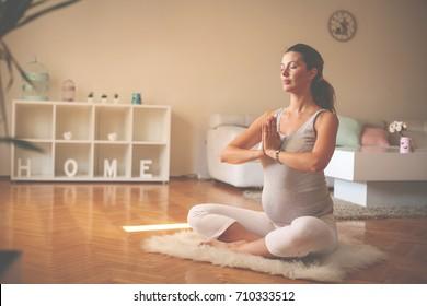 Pregnant woman meditates indoor in yoga pose. Woman enjoying in meditation.