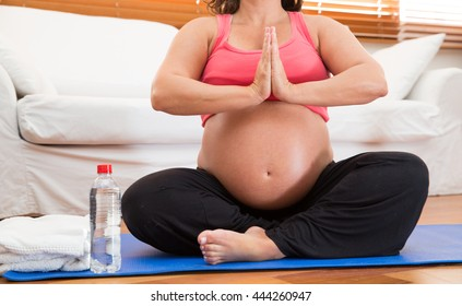 A pregnant woman meditates and practices yoga.