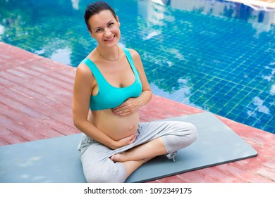 A pregnant woman is meditating near the pool. Yoga. The lotus position.