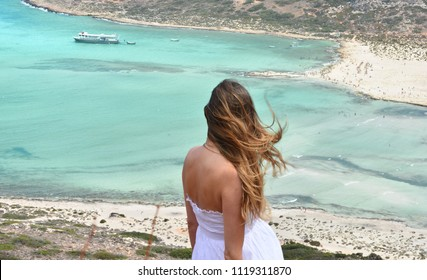 The pregnant woman observes the beautiful Balos lagoon on the island of Crete in Greece