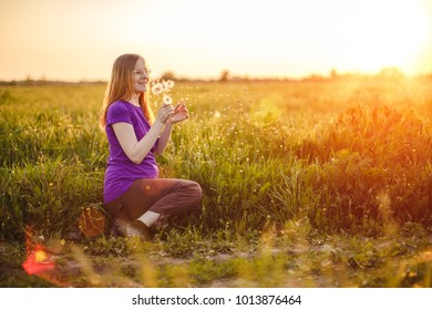 Pregnant woman on a background of sunset and nature. Beautiful young girl model with tummy in sun, in  backlight.