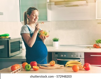 pregnant woman on kitchen making healthy fruit salad
