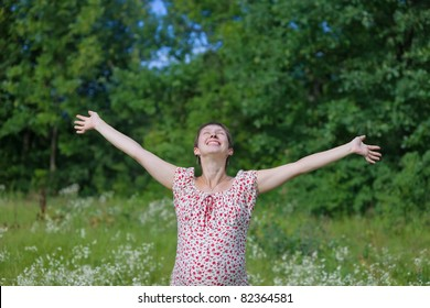 Pregnant woman with open hands in the forest