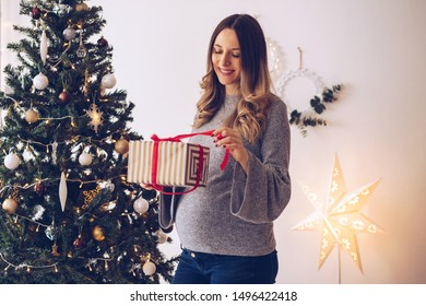 Pregnant woman opening present in front of Christmas tree