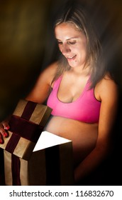 Pregnant Woman Opens a Gift Box with a Christmas Present
