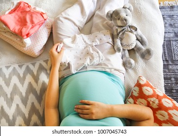 Pregnant woman is packing baby clothes for going to maternity hospital top view