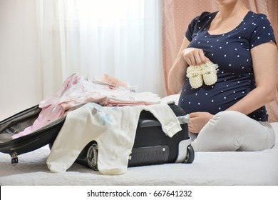 Pregnant woman is packing baby clothes for going to maternity hospital. Woman holding small pearl baby bootee on belly