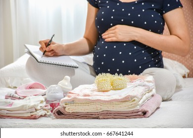 Pregnant woman is packing baby clothes for going to maternity hospital. Woman taking notes
