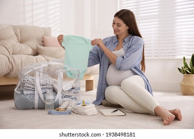 Pregnant woman packing bag for maternity hospital at home
