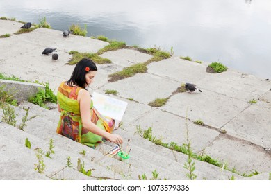 pregnant woman paints aquarelle on the margin of a lake