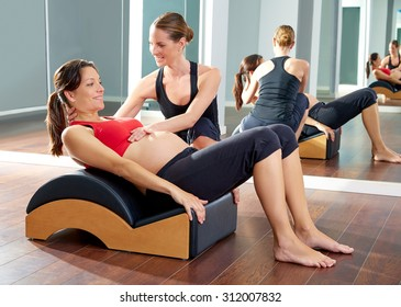 pregnant woman pilates exercise roll back with Wave corrector and personal trainer