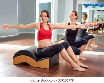 pregnant woman pilates exercise spine twist with Wave corrector and personal trainer