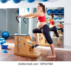 pregnant woman pilates exercise wunda chair at gym indoor