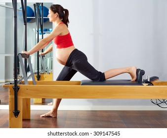 pregnant woman pilates reformer cadillac exercise workout at gym