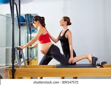 pregnant woman pilates reformer cadillac exercise workout with personal trainer