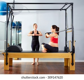 pregnant woman pilates reformer cadillac arms exercise workout with personal trainer