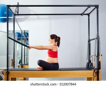 pregnant woman pilates reformer forward push through exercise workout at gym