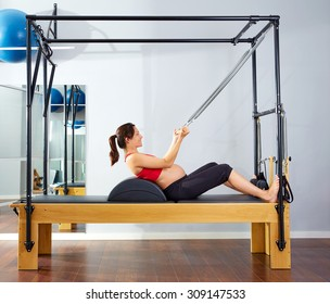 pregnant woman pilates reformer roll up cadillac exercise workout at gym