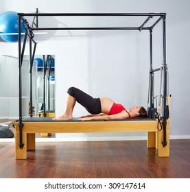 pregnant woman pilates reformer shoulder bridge  exercise workout at gym