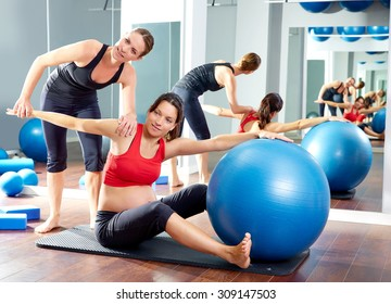 pregnant woman pilates saw exercise workout at gym with personal trainer