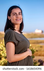 Pregnant woman poses with dress on the marshlands.