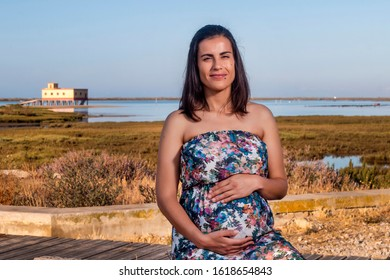 Pregnant woman poses with floral dress on the marshlands.