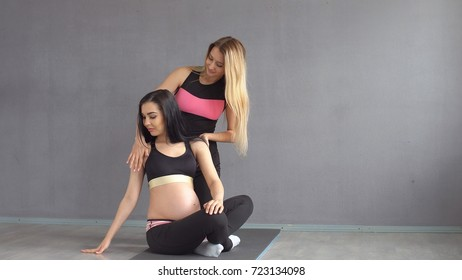Pregnant woman practicing yoga along with a fitness instructor in the gym.