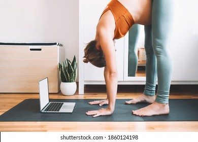Pregnant woman practicing yoga at home with laptop. Expectant mother doing prenatal video training class indoors. Female exercise, meditate during pregnancy. Online fitness class on digital devices.