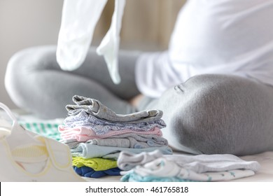 Pregnant woman is preparing baby clothes