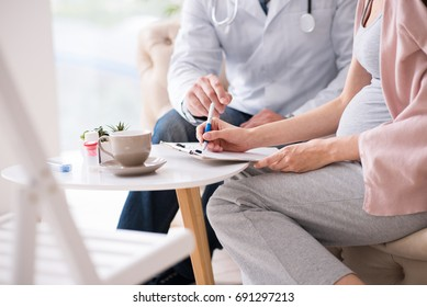 Pregnant woman putting her sign on the document