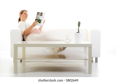 Pregnant woman reading a magazine on a couch.