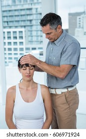 Pregnant woman receiving a head massage from masseur at the health spa