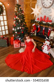 Pregnant woman in red dress posing in Christmas  decorations