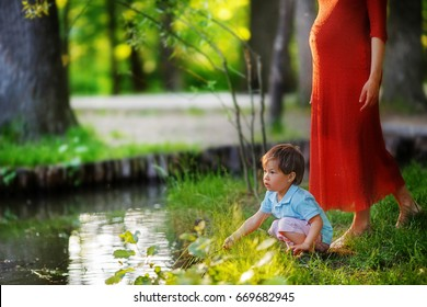 A pregnant woman in a red dress takes a step toward her eldest son. A boy is playing squatting on the lake in the middle of a green forest